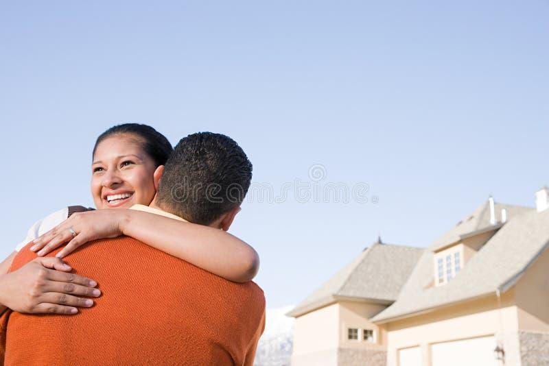 Un par que abraza fuera de su nuevo hogar fotografía de archivo