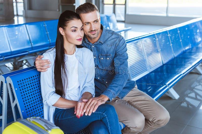 Un par que abraza y que espera el avión fotos de archivo libres de regalías