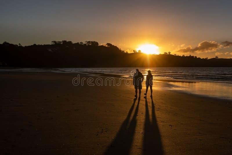 Un par que camina la playa de Oneroa, isla de Waiheke, Nueva Zelanda en una puesta del sol de oro foto de archivo libre de regalías