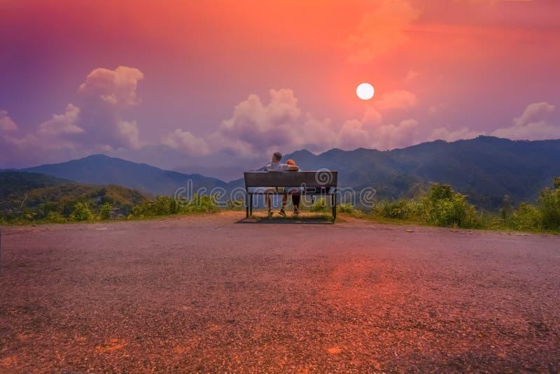 Un par que localiza en un banco que pasa por alto la puesta del sol asombrosa foto de archivo libre de regalías