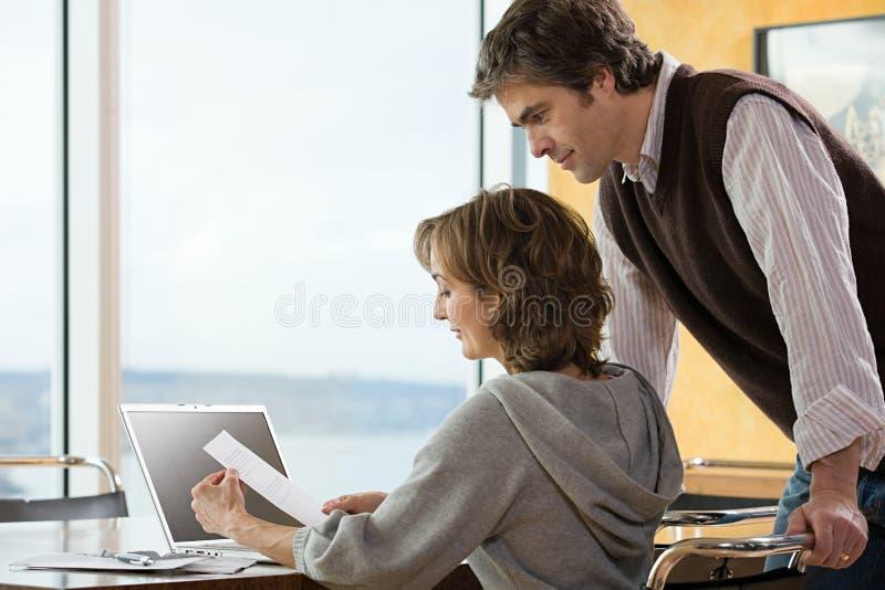 Un par que mira papeleo foto de archivo
