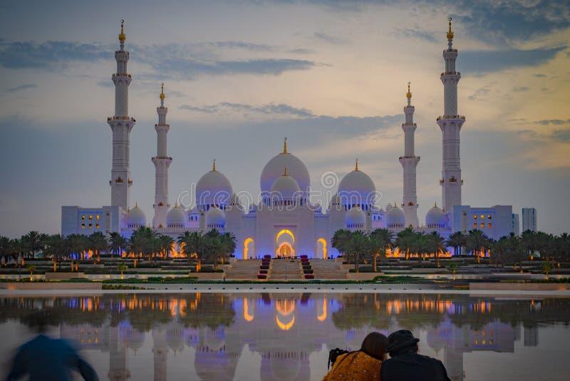 Un par que mira una vista axial de la gran mezquita de Abu Dhabi la oscuridad fotografía de archivo libre de regalías
