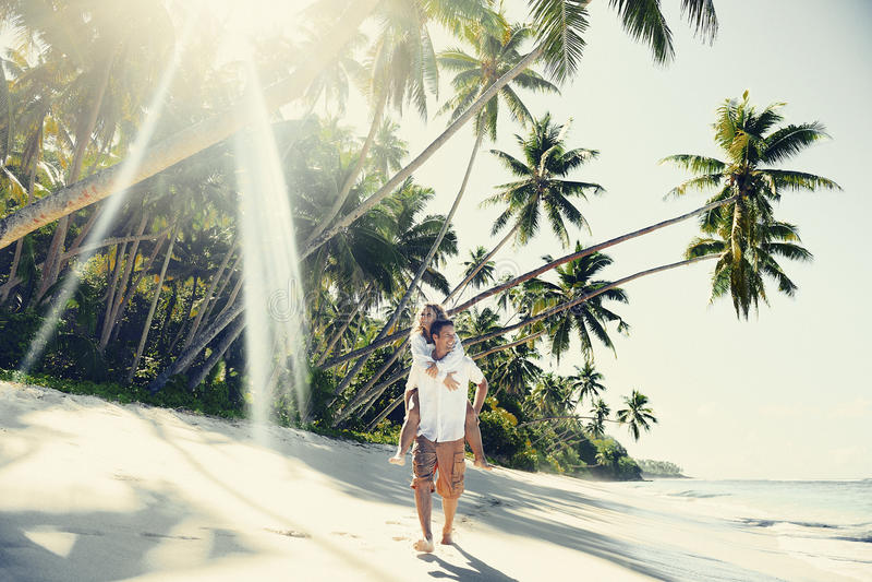 Un par que se relaja en el concepto de la playa imagen de archivo