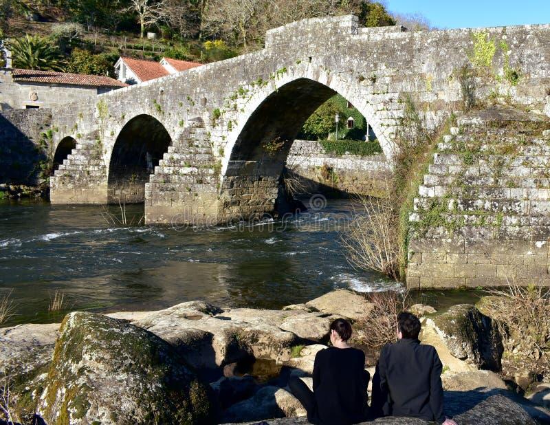 Un par que toma una rotura en un río cerca de un puente de piedra viejo Ponte Maceira, España, el 16 de febrero de 2019 imagen de archivo libre de regalías