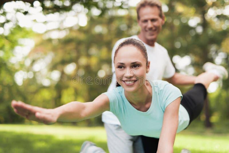 Un par se dedica a deportes en un parque caliente del verano Un hombre ayuda a una mujer a estirar fotografía de archivo
