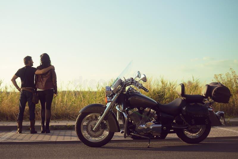 Un par se está colocando en un campo y está mirando el cielo en la distancia Los pares llegaron en una motocicleta El individuo y foto de archivo libre de regalías