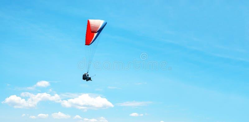 Un paracaídas colorido con el skydiver en un fondo soleado del cielo azul Forma de vida activa Deporte extremo El concepto de vac fotos de archivo