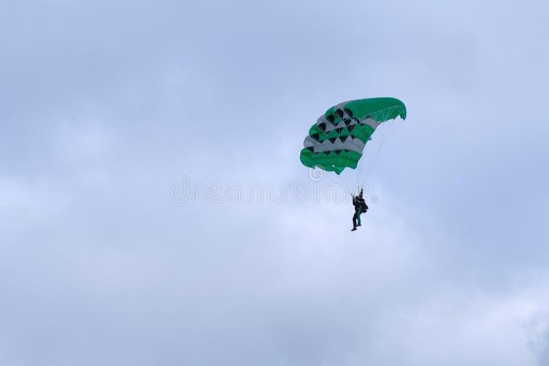 Un paracaídas verde es vuelo en el cielo imagen de archivo