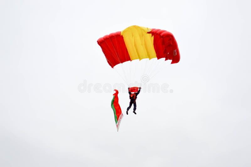 Un paracaidista con un paracaídas multicolor brillante vuela a través del cielo con la bandera del skydiver de la República de Be fotos de archivo