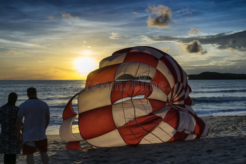 Un parachute de watchig de couples par coucher du soleil photos stock