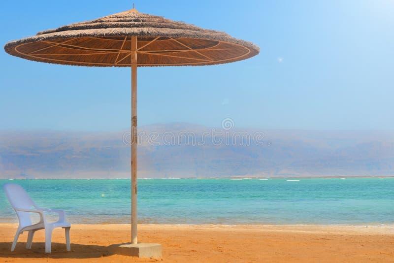 Un paraguas de la paja y un soporte blanco de la silla en una playa arenosa cerca del agua Resto en el mar muerto en Israel que p imagen de archivo