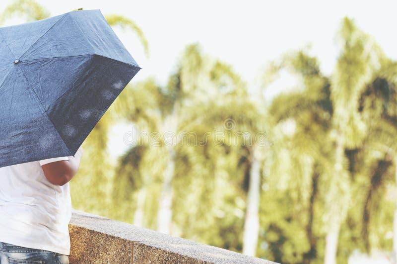 Un paraguas del control del hombre en el parque en un día fotos de archivo