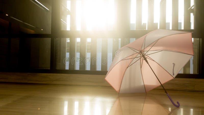 Un parapluie rose et bleu est placé sur le plancher devant la fenêtre Permettez au parapluie de sécher après pluie La fenêtre mon photos libres de droits