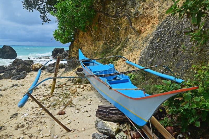 Un paraw blu tradizionale di colore ha parcheggiato sulla spiaggia all'isola di Boracay immagini stock