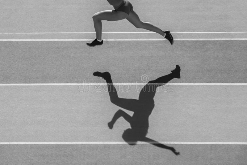 Un pareggiatore caucasico del corridore della donna che corre nella siluetta sul fondo dello stadio Colore in bianco e nero fotografie stock libere da diritti