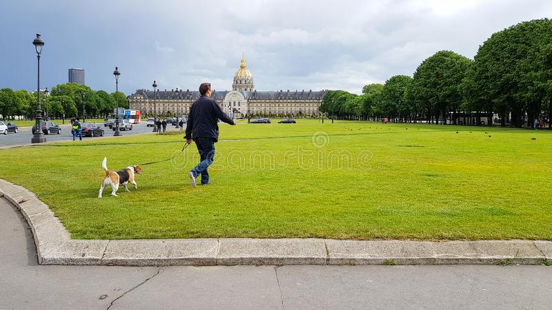 Un parigino cammina con un cane sui prati verdi nei pressi di Disabled House, Les Invalides Museum with golden dome, Parigi, Fran immagine stock libera da diritti