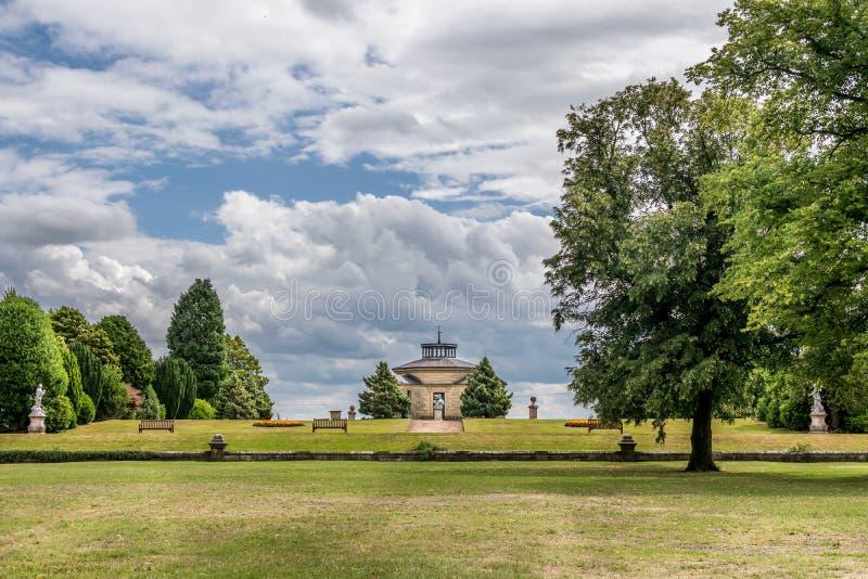 Un parque con estatuas y un pequeño edificio imagen de archivo libre de regalías