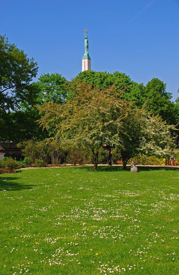 Un parque en Riga durante tiempo de verano con el monumento alto de la libertad en la parte posterior imagenes de archivo