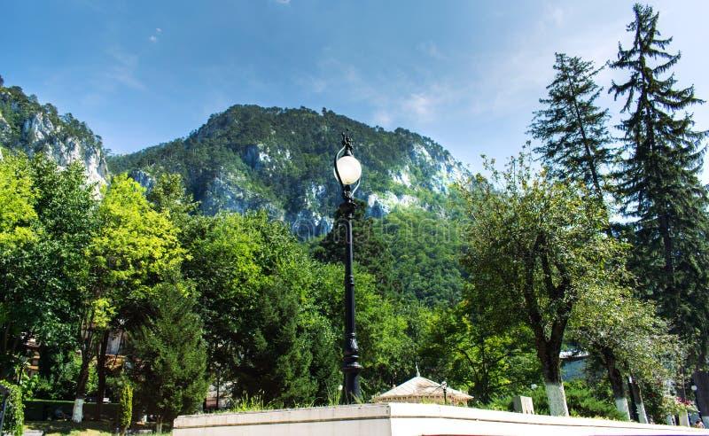 Un parque hermoso cerca de las montañas Montañas cubiertas por el bosque, rocas blancas, una linterna y las porciones de verdor,  imagenes de archivo