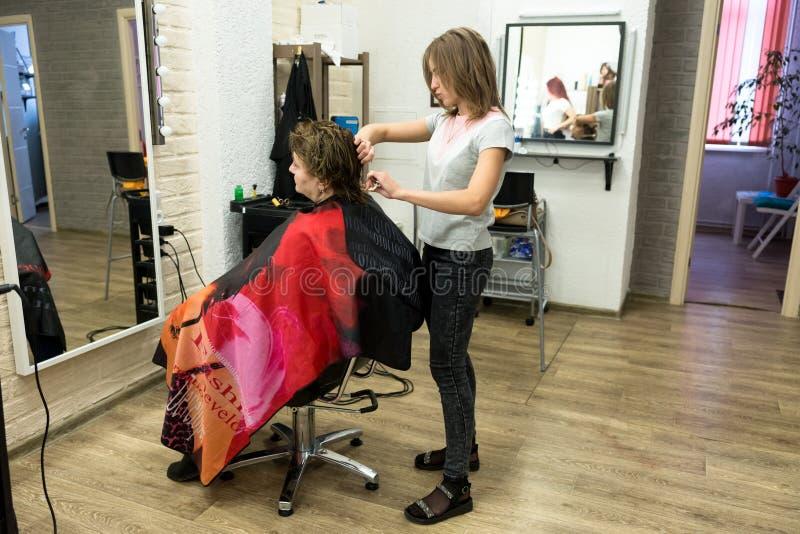 Un parrucchiere femminile taglia i capelli ad un cliente della donna in un salone di lavoro di parrucchiere, fra gli specchi, su  fotografia stock libera da diritti