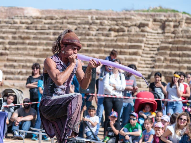 Un partecipante del festival di Purim mostra una prestazione con una palla gonfiabile per gli ospiti a Cesarea, Israele immagine stock libera da diritti