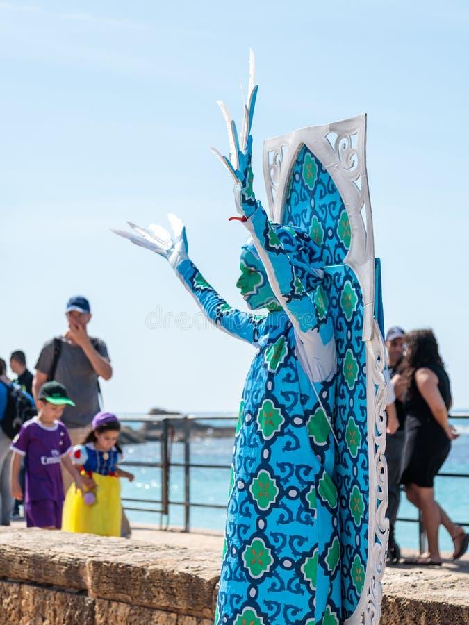 Un partecipante di festival dedicato ai supporti di Purim si è vestito in un costume leggiadramente della statua a Cesarea, Israe immagini stock libere da diritti