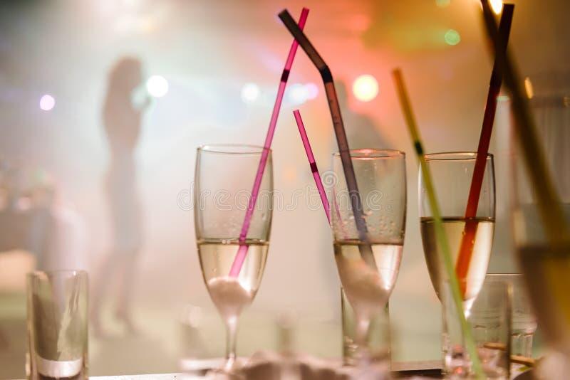 Un partido en un club nocturno, vidrios del champán con la paja imágenes de archivo libres de regalías