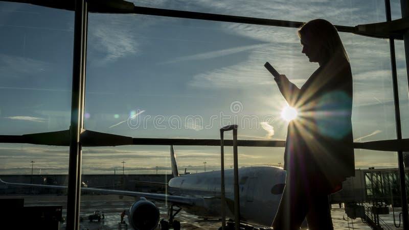 Un pasajero femenino con un teléfono en la ventana terminal de aeropuerto foto de archivo libre de regalías