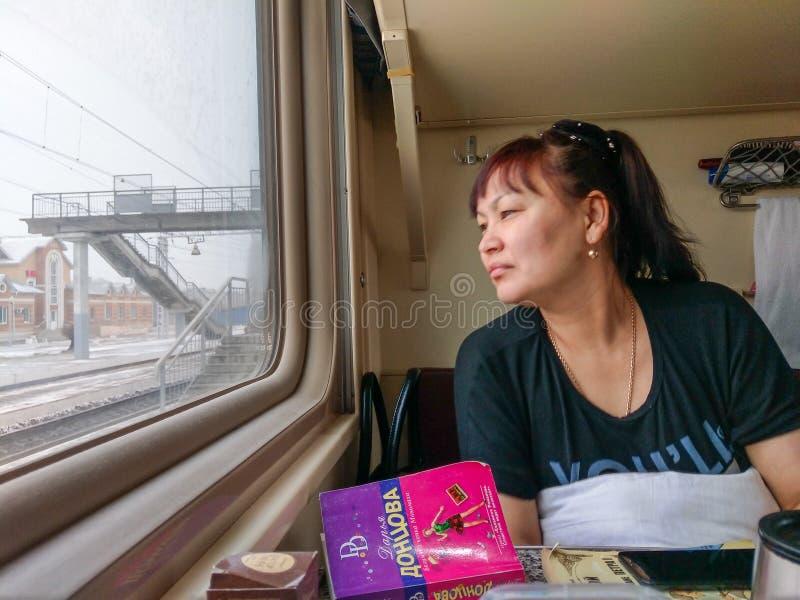Un pasajero viaja en un tren de Moscú-Vladivostok y mira hacia fuera la ventana foto de archivo