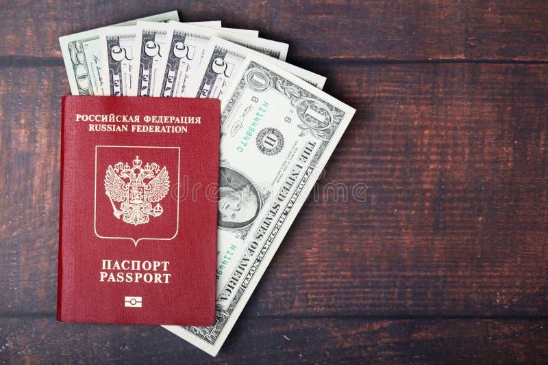 Un pasaporte con los billetes de banco americanos del dólar dentro como concepto del trabajo y el viajar imagenes de archivo
