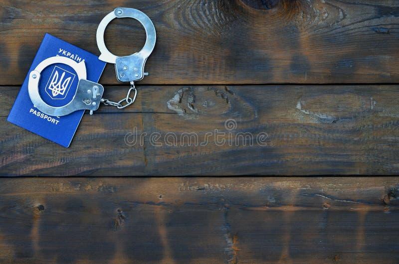 Un pasaporte ucraniano con las esposas de la policía miente en una tabla de madera Problemas con la ley durante la travesía de la imágenes de archivo libres de regalías