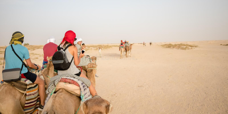 Un paseo de la muchacha en el camello en el desierto del Sáhara, Túnez, África imagenes de archivo