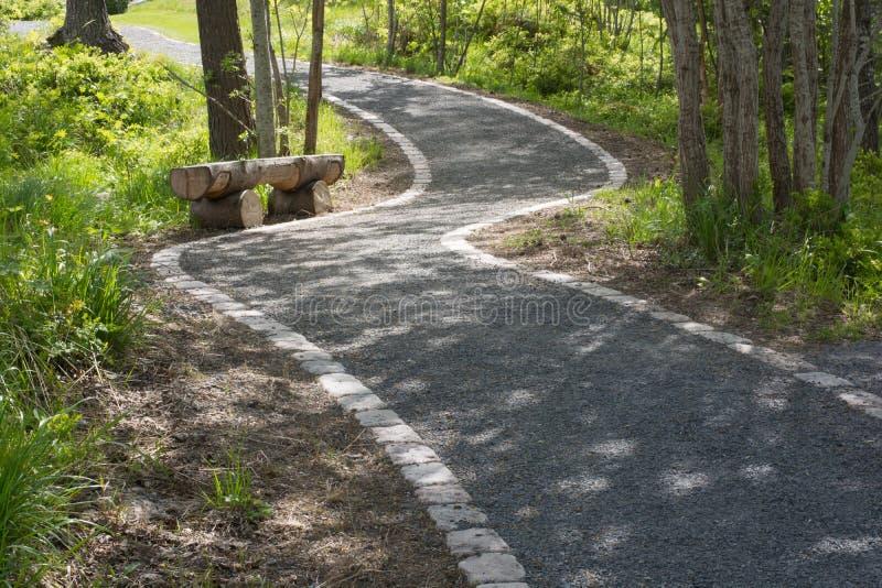 Un passage couvert en parc avec un banc en bois sur le côté photo stock