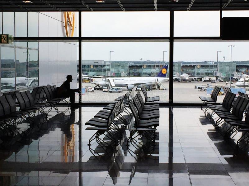 Un passeggero solo visto in siluetta che aspetta nell'aeroporto di Francoforte fotografia stock libera da diritti