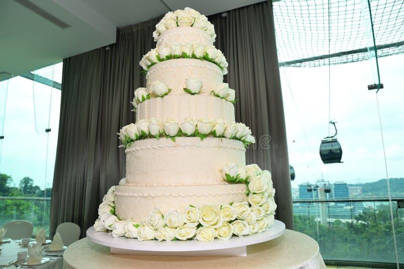Un pastel de bodas de cinco capas de la grada color crema en color con los desmoches de las rosas blancas stock de ilustración