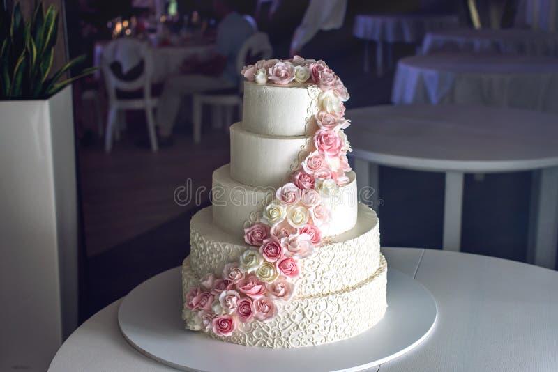 Un pastel de bodas con gradas grande adornado con las rosas rosadas en la tabla en el restaurante imagenes de archivo