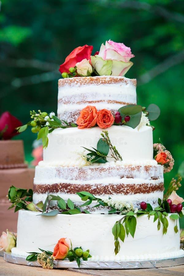 Un pastel de bodas del chocolate con helar blanco y flores rojas, rosadas, y anaranjadas con las hojas verdes - serie del pastel  imágenes de archivo libres de regalías