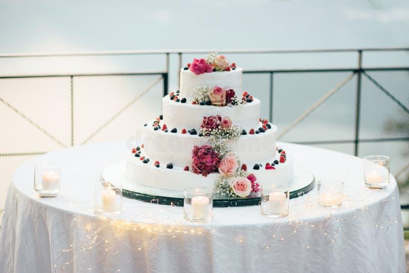 Un pastel de bodas hermoso en cuatro niveles está en la tabla contra la perspectiva del lago pintoresco fotos de archivo libres de regalías