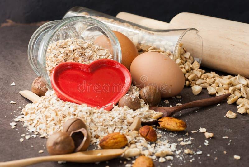 Un pasto asciutto sano dell'avena con il dado e cuore rosso in un cucchiaio di legno fotografia stock