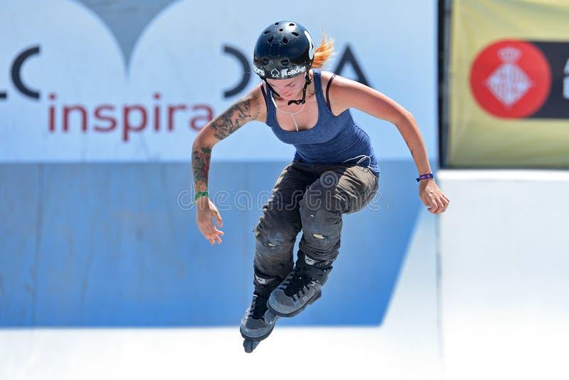 Un patinador profesional en la competencia patinadora en línea de las mujeres en los juegos extremos de Barcelona de los deportes imagen de archivo