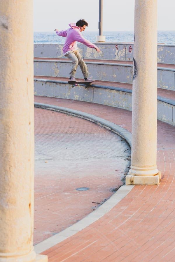 Un patineur font une glissière de queue de frondide avec la planche à roulettes photo stock