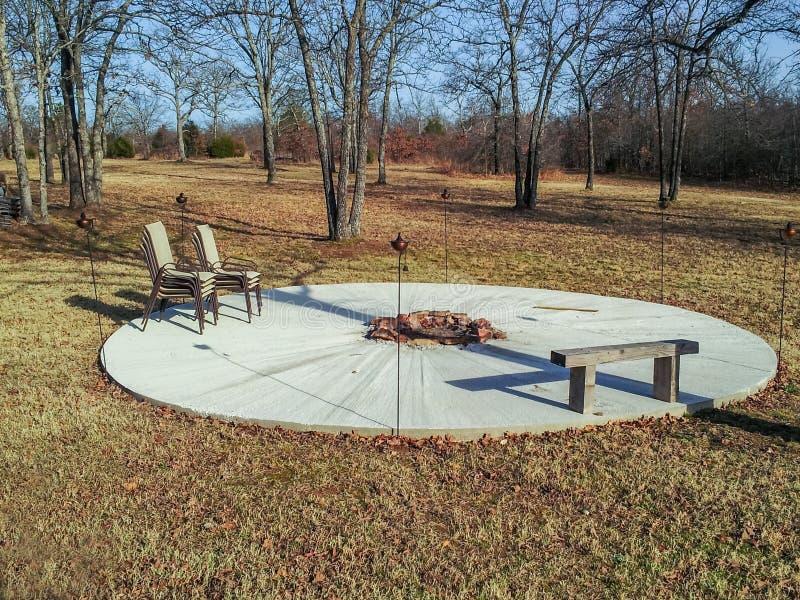 Un patio redondo del cemento con un hoyo del fuego en el banco medio y de madera y sillas y antorchas apiladas del tiki del metal fotografía de archivo libre de regalías