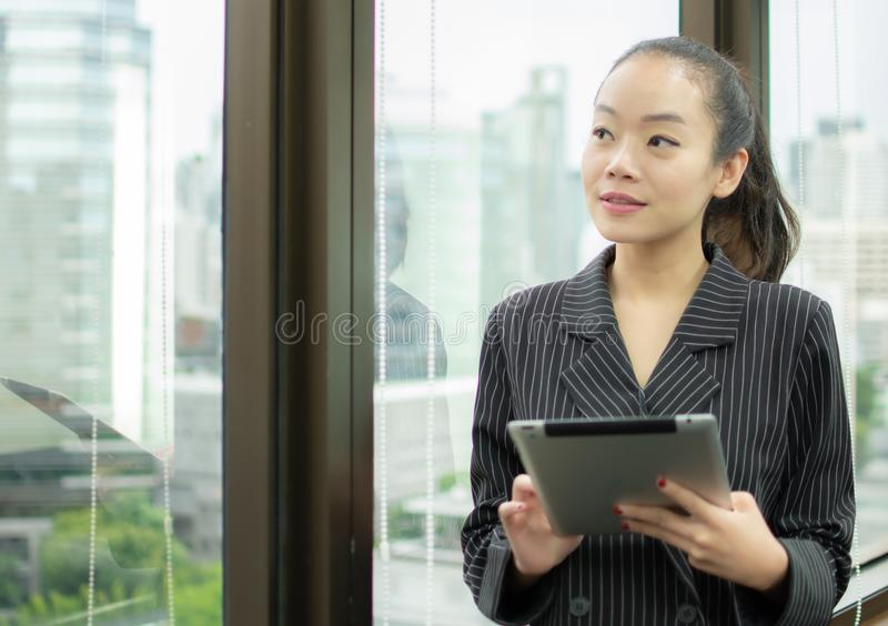 Un patron emploie le comprimé et la position près de la fenêtre photos libres de droits