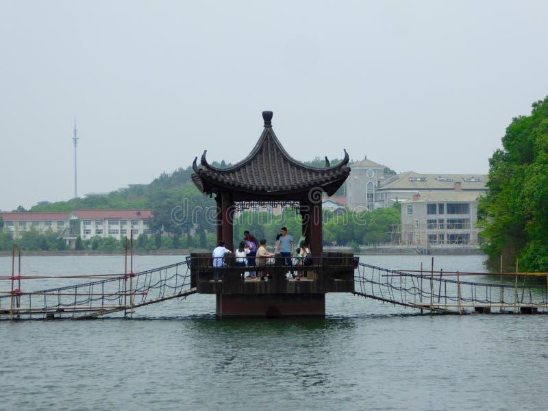 Un pavillon au-dessus du lac avec des touristes restant à l'intérieur image libre de droits
