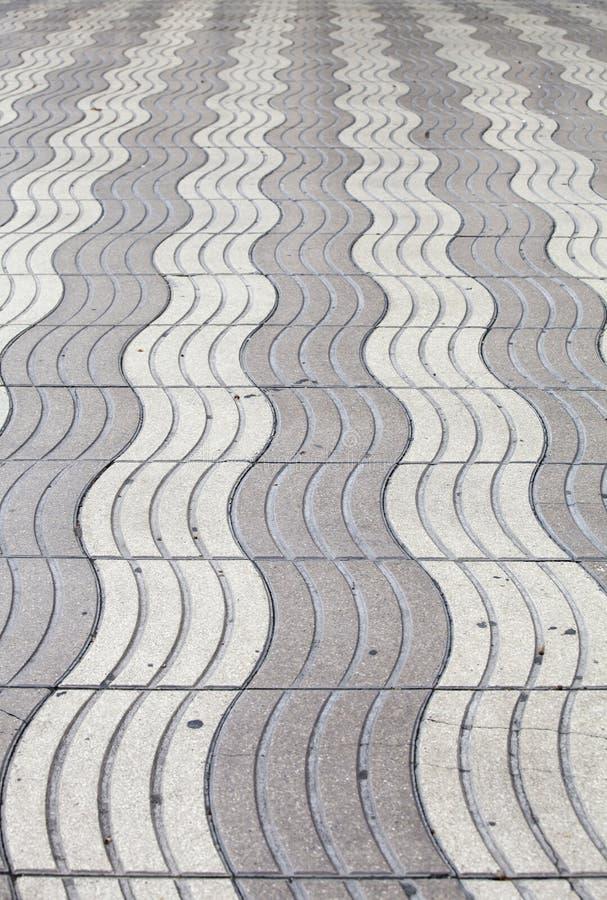 Un pavimento grigio ondulato all'infinito fotografia stock