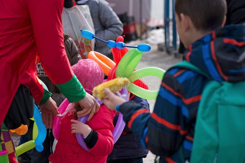 Un payaso independiente que crea animales del globo y diversas formas en el festival al aire libre en centro de ciudad imagen de archivo libre de regalías