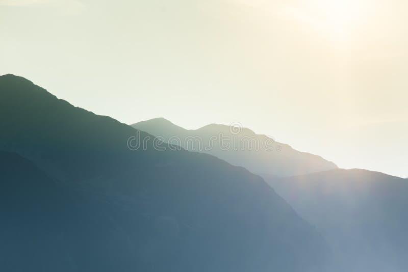 Un paysage rêveur et flou de montagnes près de coucher du soleil Flasre de Sun et regard brumeux dans des tons bleus Paysage de m photographie stock libre de droits