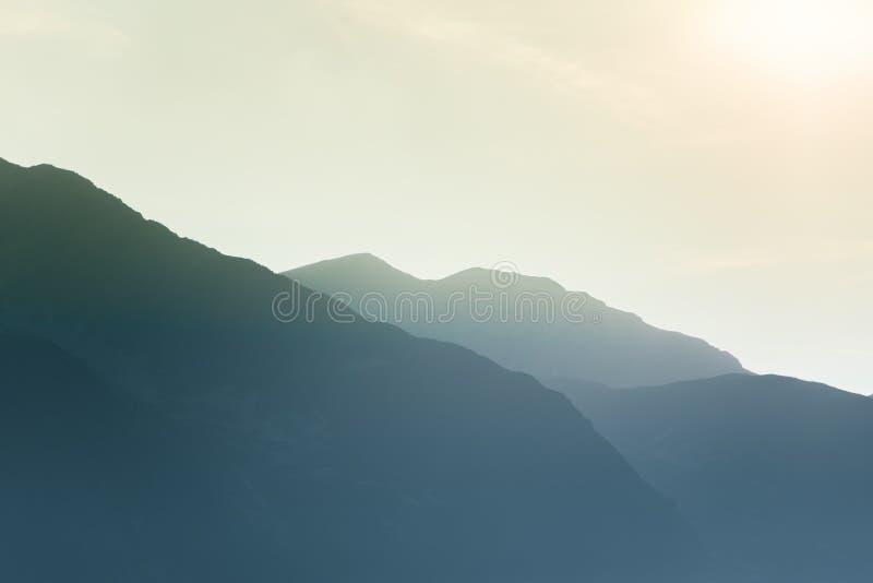 Un paysage rêveur et flou de montagnes près de coucher du soleil Flasre de Sun et regard brumeux dans des tons bleus Paysage de m photos libres de droits