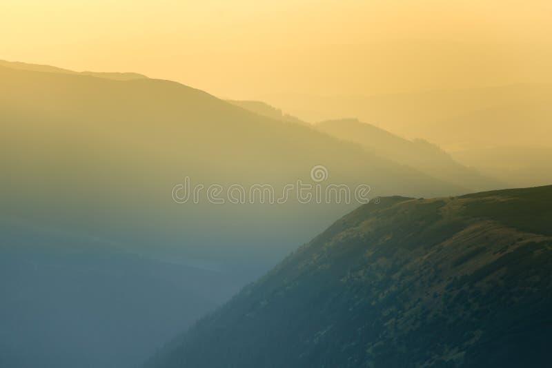 Un paysage rêveur et flou de montagnes près de coucher du soleil Flasre de Sun et regard brumeux dans des tons bleus Paysage de m photo stock