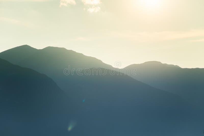 Un paysage rêveur et flou de montagnes près de coucher du soleil Flasre de Sun et regard brumeux dans des tons bleus Paysage de m images stock